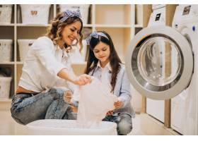 母亲和女儿在自助洗衣店洗衣服_6636867