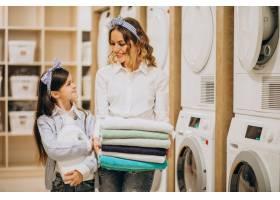 母亲和女儿在自助洗衣店洗衣服_6636883