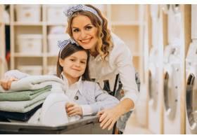 母亲和女儿在自助洗衣店洗衣服_6636941