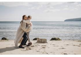 母亲和女孩在海滩上拥抱_11105722