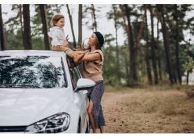 母亲和她的儿子在停车场的车旁_10298356