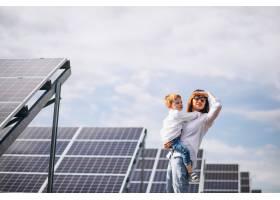母亲和她的小儿子在太阳能电池板旁_5175791