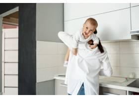 母亲在厨房里和小婴儿玩耍_9696752