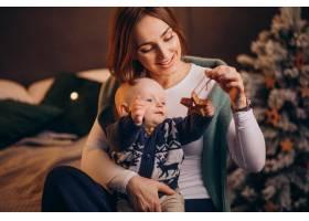 母亲带着她的男婴庆祝圣诞节_11981348