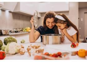 母亲带着小女儿在厨房里一起做饭_6213245