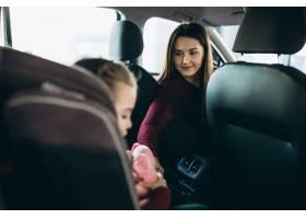 母亲带着小女儿坐在汽车后座的汽车座椅上_6426737