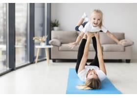 母亲在家中带着笑脸的孩子锻炼的前景_7435759