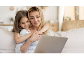 母亲在家中用笔记本电脑工作女儿拥抱着她_10604664