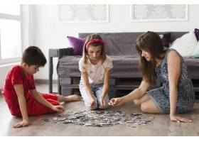 母亲在家里和孩子们玩拼图游戏_5127643
