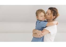 母亲在家里拥抱她的小女儿_7936882