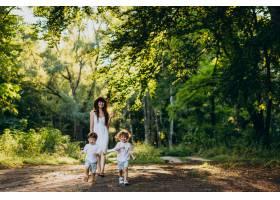 母亲带着两个儿子在公园里玩耍_10298748