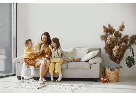 母亲带着女儿和儿子在家做一个节日篮子_13272765