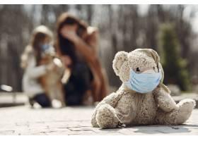 母亲带着女儿戴着口罩走在外面_7710659