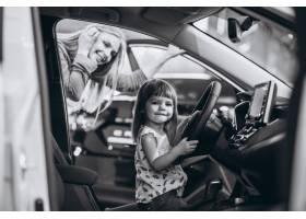 母亲带着小女儿坐在汽车展厅的一辆车里_5157784
