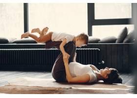 母亲带着年幼的儿子在家做瑜伽_4209513