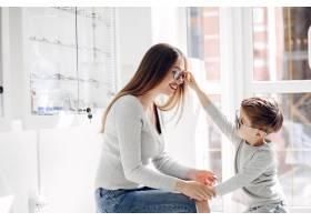母亲带着年幼的儿子在眼镜店里_5011906