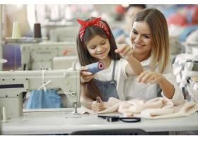 母亲带着年幼的女儿在工厂缝制衣服_6632296