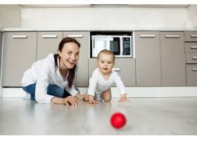 母亲微笑着看着婴儿爬在地板上接球_9696760