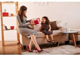 年轻女子给女儿送礼物母亲和孩子在节日里_12431948