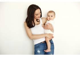 年轻快乐的母亲微笑着隔着白墙看着她的小_9028789