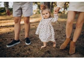 年轻的一家人带着可爱的小女儿在夕阳的森林_10298408