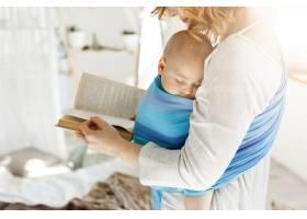 年轻母亲在舒适明亮的卧室里为刚出生的小儿_8811774