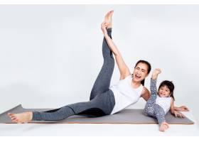 年轻母亲用体操训练可爱的女儿_5153090