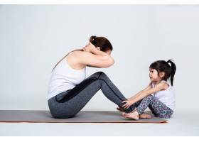 年轻母亲用体操训练可爱的女儿_5153092