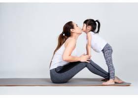 年轻母亲用体操训练可爱的女儿_5153093