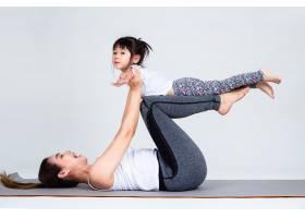 年轻母亲用体操训练可爱的女儿_5153094