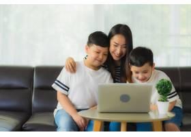 年轻漂亮的亚裔女性妈妈和她的两个儿子在沙_7531803