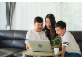 年轻漂亮的亚裔女性妈妈带着两个儿子在沙发_7756070
