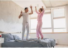 年轻漂亮的夫妇早上在床上玩得很开心独自_9699649