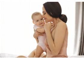 年轻漂亮的妈妈穿着睡衣微笑着拥抱亲_9321540
