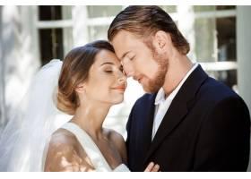 年轻漂亮的新婚夫妇闭着眼睛微笑享受着_7599917
