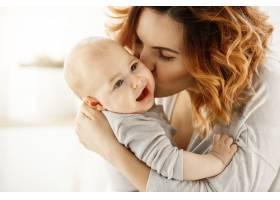 年轻漂亮的母亲亲吻他哭泣的婴儿的特写孩_8811601
