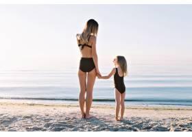 年轻漂亮的母亲和穿着黑色泳衣的小女儿在夏_12965035