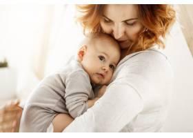 年轻漂亮的母亲温柔地拥抱着她可爱的小孩子_8811597