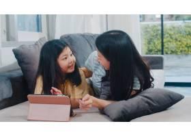 年轻的亚洲家庭和女儿在家中快乐地使用平板_6142516