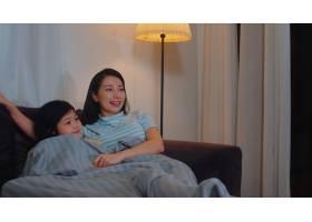 年轻的亚洲家庭和女儿晚上在家看电视韩国_6142527