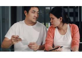 年轻的亚洲怀孕夫妇在家里记录收入和支出_6141952