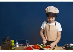 穿着围裙和帽子的专注的男童厨师为素食千层_10897548