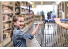 穿着蓝色衬衫的母女俩用手推车在超市购物_10107645