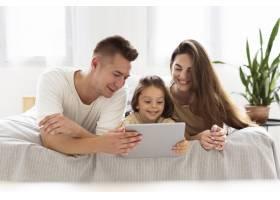 美丽的一家人看着平板电脑_10700476