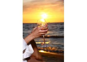 美丽的年轻女子在海滩上喝酒_6451749