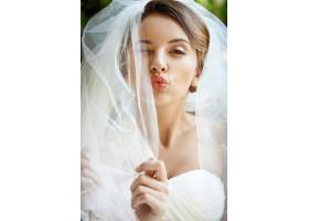 美丽的新娘穿着婚纱戴着面纱眨着眼睛送_7599912