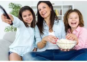 美丽的母亲和她的女儿们在家里吃爆米花_1139634