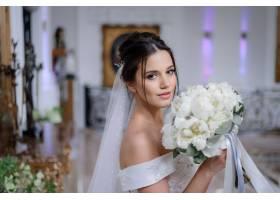 美丽的黑发白人新娘手持一束白牡丹直视室_7497129