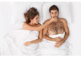 近距离观察躺在床上的一对夫妇他们盖着白_12950743