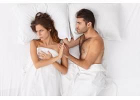 近距离观察躺在床上的一对夫妇他们盖着白_12951057